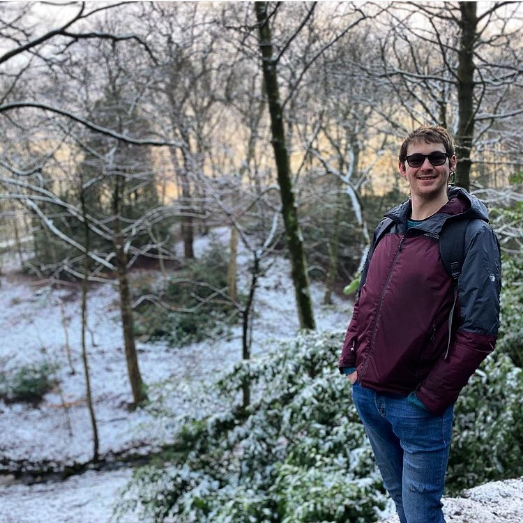 Tall man stood with a snowy woodland background